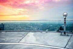 Jumelles ou télescope tenues dans la main sur le gratte-ciel Photos libres de droits