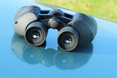 Jumelles se trouvant sur le capot de voiture. Photographie stock libre de droits