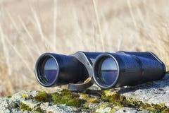 Jumelles sur la pierre dans la steppe pendant l'été C'est équipement important pour le voyageur photo stock