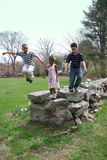 Jump. Kids having fun jumping of of the rocks Stock Image