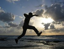 Jump. Man running and jumping on the beach Stock Image