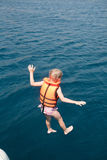 Jump. Little girl in life jacket jumping to sea water Stock Photo