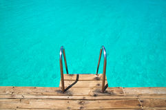 Jump in!. Empty turquoise water and a ladder Stock Images