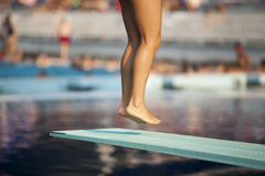 Jump. A girl preparing to jump into a swimming pool Stock Photography