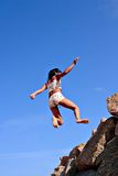 Jump !. A girl jumps from the rocks Stock Photos