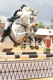 Jump. Ing white horse. Equestrian event Royalty Free Stock Images