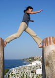 The Jump. The girl bravely jumping over a fort wall gap with a cemetery and San Juan old city in a background (Puerto Rico Stock Photo