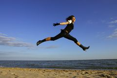 Jump. Girl is jumping over the sea and this jump is like a fly Royalty Free Stock Images