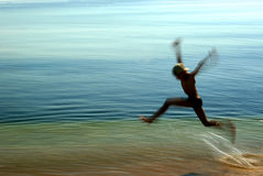 Jump. Little boy jumping on sea - motion effect stock photo