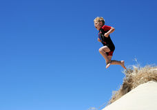 Jump. Boy jumping from the top of a sand dune Stock Images