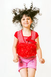 In Jump. Portrait of pretty young jumping girl over grey background Royalty Free Stock Images