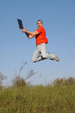 Jump. With traveling PC. Man in red t-shirt Royalty Free Stock Photos