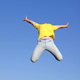Jump. Boy in yellow t-shitt on blue background Stock Photos