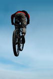 Jump. Mountain biker jumping from the rock on downhill competition Stock Image