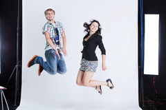 Jump around in the studio. Young men and a women jumping in a photo studio Royalty Free Stock Photo