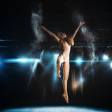 Jump of ballerina on stage in theatre against spotlights Royalty Free Stock Photo