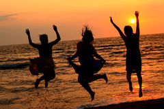 Jump at the Beach. Silhouette of 3 women jumping on a beach during sunset Royalty Free Stock Images