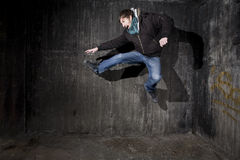 Jump - breakdance concept. Man jumping in old black grungy room corner with shadows - breakdance concept Royalty Free Stock Image
