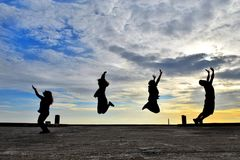 They jump on the bridge gestures evening sun sets three and four. Three, bridge, jump, four, background, sun, nature, young, people, person, girl, happy, summer Royalty Free Stock Image