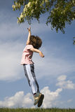 Jump of child for the flower. Spring Royalty Free Stock Image
