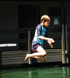 Boy gathers courage and jumps in the water. A child jumping from the diving board at the local lake Royalty Free Stock Photography
