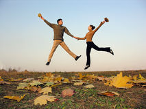 Jump couple autumn leaves stock images