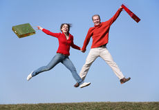Jump couple with bags Royalty Free Stock Photography