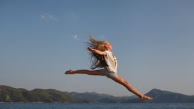 The jump. Flight above the sea  and mountains of the young girl about 9-12 years old with the blonde and loose hair in the rays of the setting sun. She wears Royalty Free Stock Photos