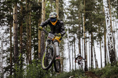 Jump and fly racer on bike in woods Royalty Free Stock Images