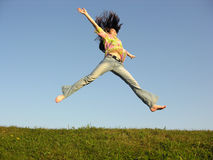Jump girl with hair on sky. Green grass stock image