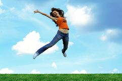 Jump girl over a grass Royalty Free Stock Image