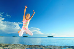 Jump Girl And Sea. Happy jump girl and sea in the background of blue sky Royalty Free Stock Photography