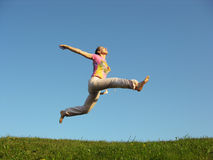 Jump girl under sky. Green grass Stock Photo