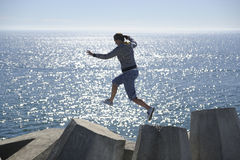 Jump!. A healthy young woman jumps for one dolos to another on the Cape Town coast, South Africa Stock Photo