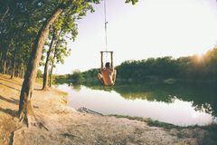 Free Jump Into The Water. A Man Is Resting On The Lake. A Swing From A Rope And A Stick. Active Recreation In Nature. Summer Fun. A Man Stock Photos - 131527313