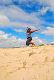 Jump for joy. An African American woman with black hair and happy smiling facial expression jumping bare feet with joy in the air on a beach in front of blue sky Royalty Free Stock Photography