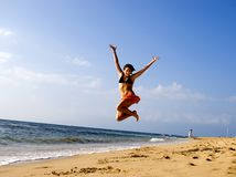 Jump for joy. Attractive young woman is jumping in the air on a tropical beach in Hawaii Stock Images