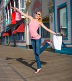 Jump for Joy. A young lady jumps for joy after leaving the mall stock photo