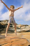 Jump for joy. Enthusiastic child burns off energy star jumps Stock Images