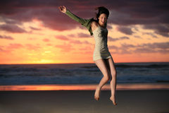 Jump for joy. Happy girl jumps for joy on beach with sunrise in background Royalty Free Stock Photo