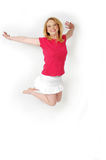 Jump for Joy. Happy blond woman jumps in the air. Full body shot on white background Stock Images