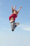 Jump for joy. Little girl jumping high in the blue sky Royalty Free Stock Photography