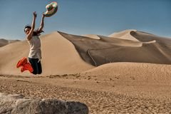 Jump of joy at Mingsha sand dunes Stock Images