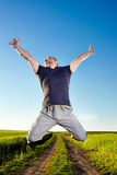 Jump for joy in the wheat field. Young man jumping for joy over a rural road crossing a wheat field Royalty Free Stock Photography