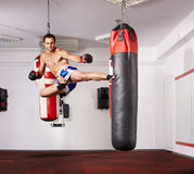 Jump kick. Kickboxer deploying a jump kick on a punchbag in the gym royalty free stock images