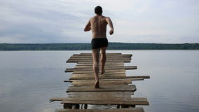 Jump in the lake. Jump in a lake with wooden walkways
