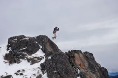 Jump of a man. From a cliff into a snowy valley Royalty Free Stock Photos