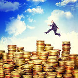 Jump on money. Businessman jump over euro coin piles Royalty Free Stock Photo