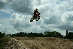 Jump. Motocross rider jumping high at a jump Royalty Free Stock Image