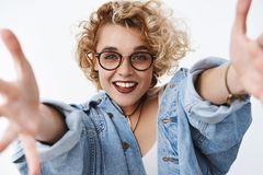 Jump into my warm arms. Friendly passionate and happy young good-looking girlfriend with blond short hairstyle wearing. Makeup and glasses stretch hands towards stock photos